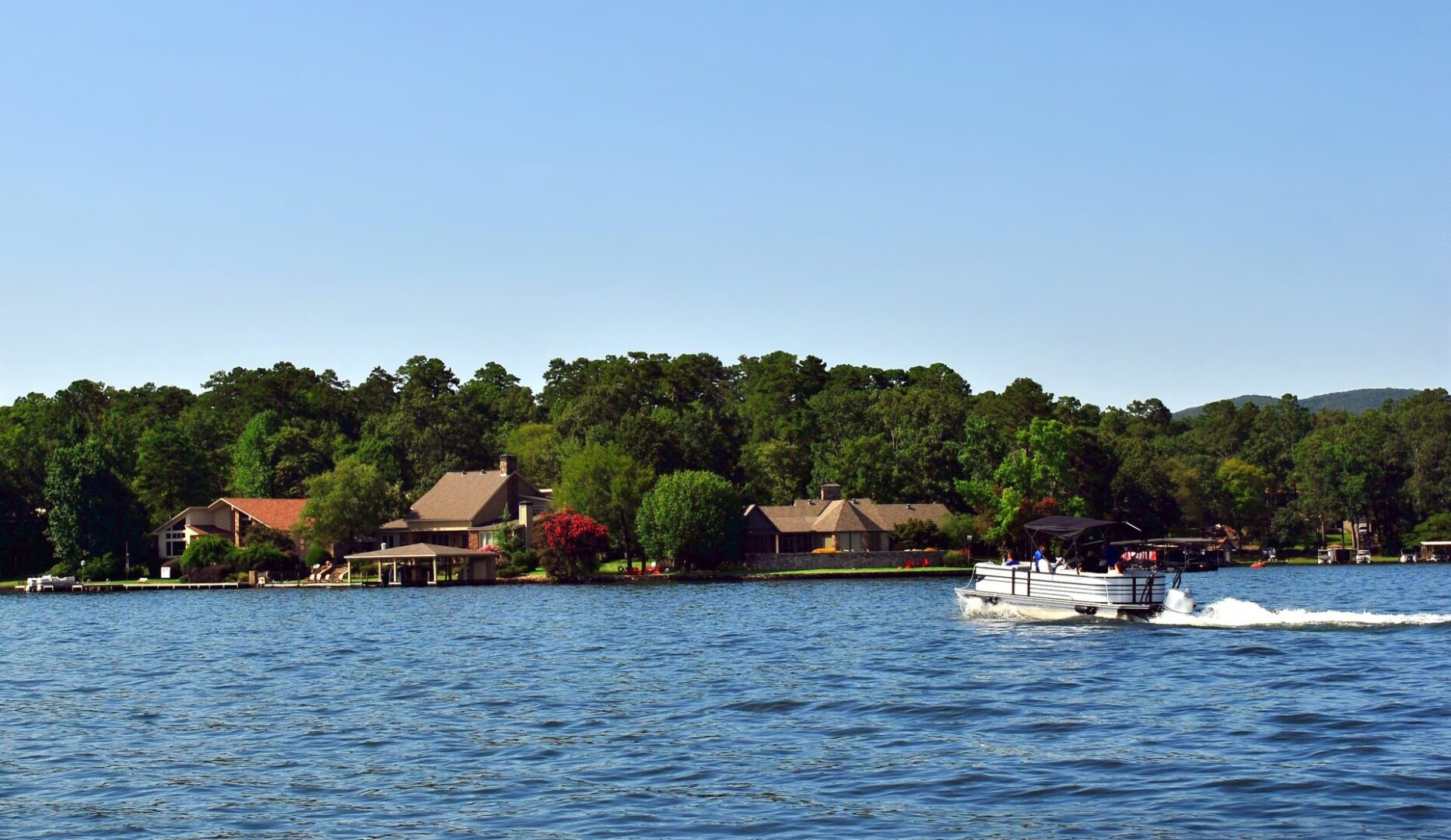 Beautiful scenic view of lake houses on the shoreline with a pontoon boat in the water.